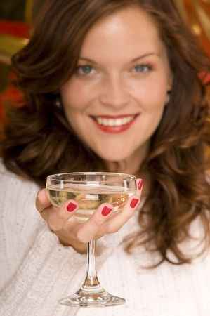 Portrait of beautiful lady toasting with a coupe of champagne, blurred background photo