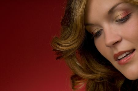 Close-up of beautiful lady on Christmas red background watching down Stock Photo - 3794923