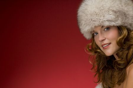 Beautiful lady looking like a princess with a fur hat on red background Stock Photo - 3794932