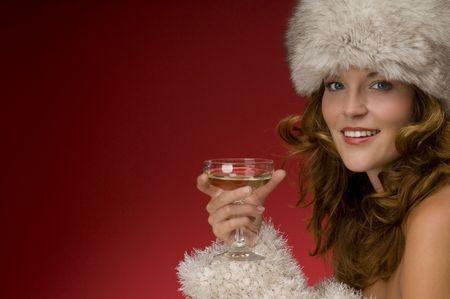 Beautiful lady with fur hat toasting with champagne on red background photo