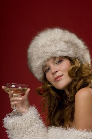 Beautiful lady with fur hat toasting with champagne on red background Stock Photo - 3794940