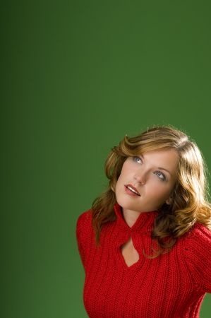 Dark blond beauty looking up on Christmas green background with red sweater Stock Photo - 3794919