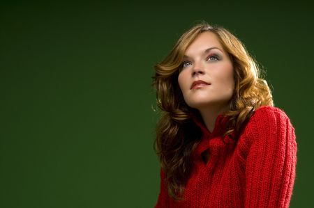 Dark blond beauty awaiting on Christmas green background with red sweater Stock Photo - 3794920