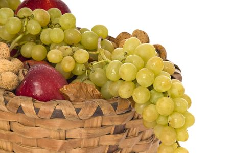 Wicker basket full of fruits on white background photo