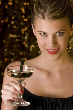Attractive young woman toasting with glass of champagne in front of out of focus Christmas lights Stock Photo - 3837000