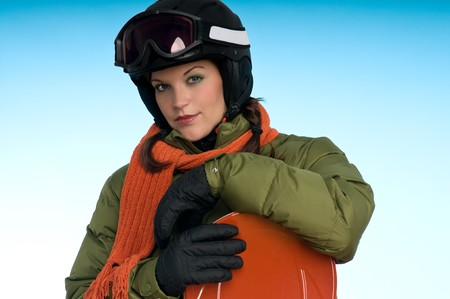 Sexy snowboard girl in green and orange on blue background photo