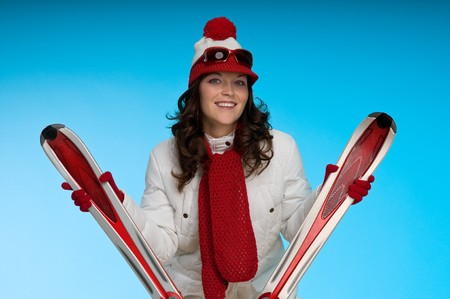 Smiling young woman in red and white skiing outfit on blue background