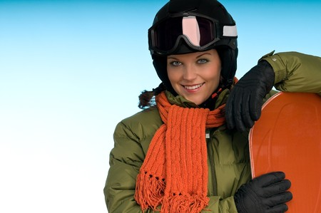 Smiling girl with orange snowboard on blue background photo