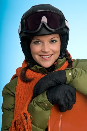 Fashion model wearing snowboard equipment on blue background photo