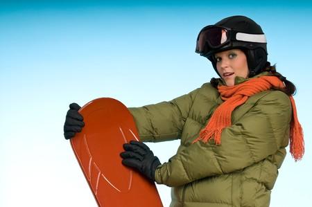 Young fashion model holding orange snowboard on blue background photo
