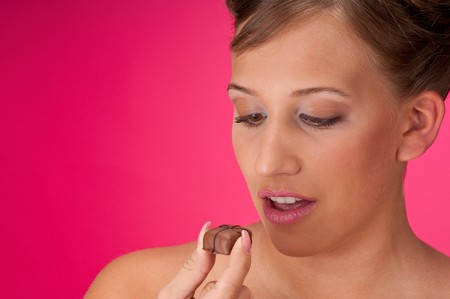 Beautiful model watching candy on pink background Stock Photo - 4242963
