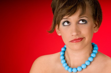 Young model with blue beads on red background Stock Photo - 4242959