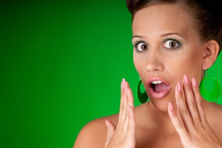 Shocked young woman on green background photo