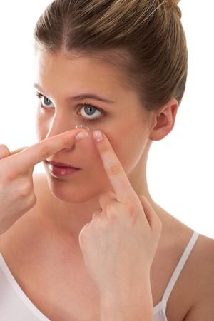 흰색 배경에 콘택트 렌즈를 적용하는 젊은 아가씨