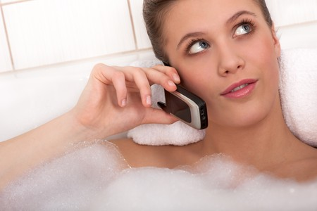 Young woman in the bathtub using mobile phone Stock Photo - 4542235