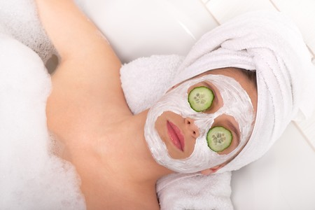 Young lady with facial mask and cucumber on eyes Stock Photo - 4542230