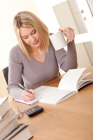 Blond girl writing homework Stock Photo - 4570509