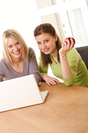 Two smiling girls watching laptop Stock Photo - 4570502