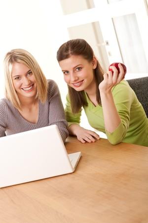 Two smiling girls watching laptop Stock Photo - 4570502