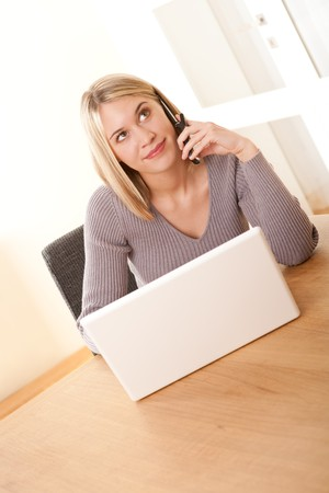 Blond woman using mobile phone and laptop, sitting at wooden table Stock Photo - 4570493