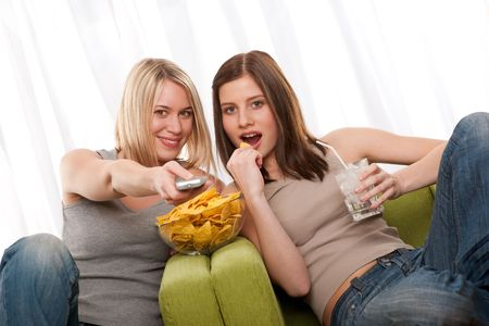 Two teenage girls watching TV and eating potato chips