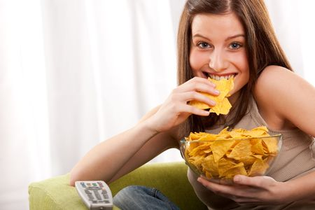 Young woman eating potato chips in front of TV Stock Photo