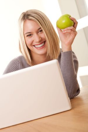 Smiling blond student working with laptop and eating apple
