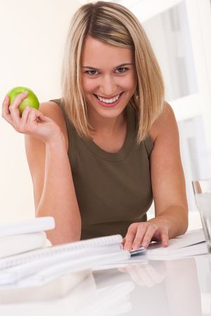 Smiling young woman sitting at white table and holding apple photo