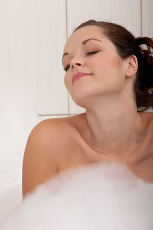 Beautiful young woman in the bathtub with foam photo