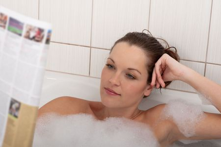 Young woman with magazine in the bathtub photo