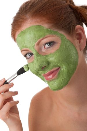 bodycare: Young woman with facial mask on white background
