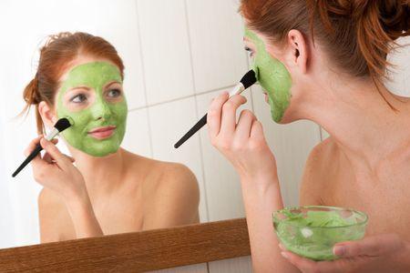skincare facial: Young woman applying green facial mask in the bathroom