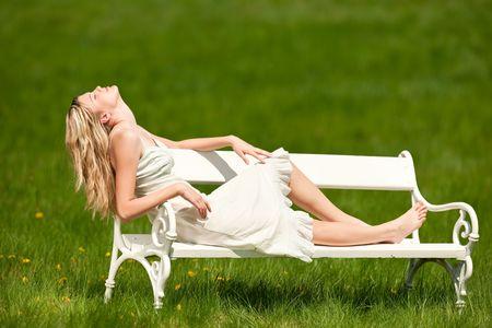 Blond young woman eyes sitting on white bench, enjoying sun photo