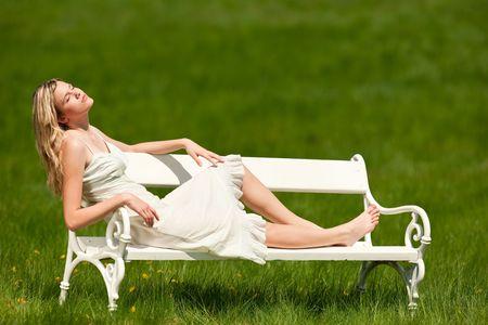 Blond giovane donna seduta sulla panchina bianca, godendo domenica; shallow DOF