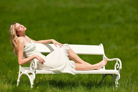 Blond young woman sitting on white bench, enjoying sun; shallow DOF Stock Photo
