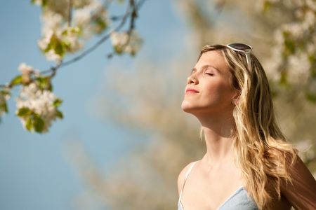 Long hair blond woman in blue dress enjoying sun under blooming tree photo