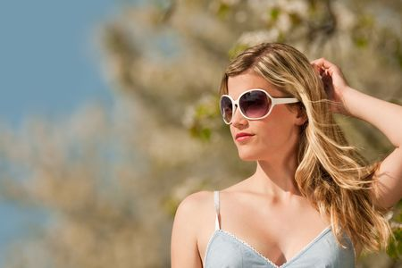 Blond woman with sunglasses standing under blooming tree and enjoying sun photo