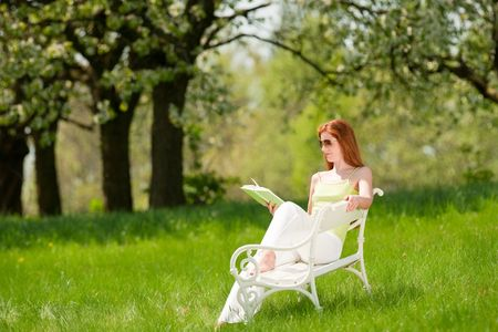 long red hair woman: Long red hair woman reading book on white bench in green meadow, shallow DOF Stock Photo