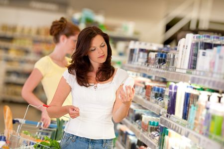 beauty shop: Brown hair woman in cosmetics department holding bottle of shampoo Stock Photo