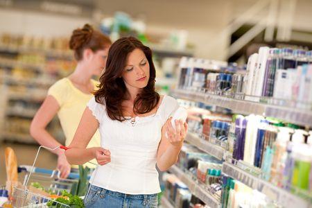 carro supermercado: Cabello casta�o mujer departamento de cosm�ticos en la celebraci�n de una botella de champ�
