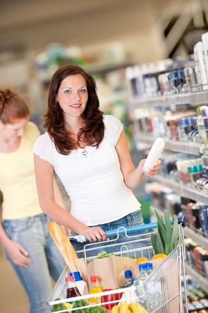 Brown hair woman with cart holding shampoo Stock Photo - 4893176