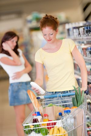 Red hair woman holding bottle of shampoo in a supermarket photo
