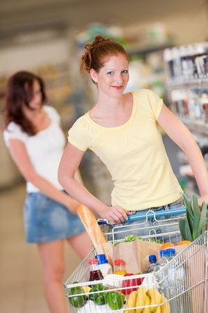 Red hair woman with cart in a shopping mall photo