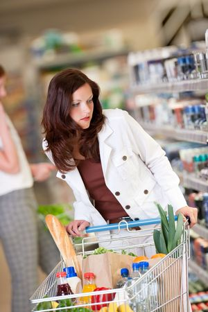Brown hair woman with a shopping cart in a supermarket photo