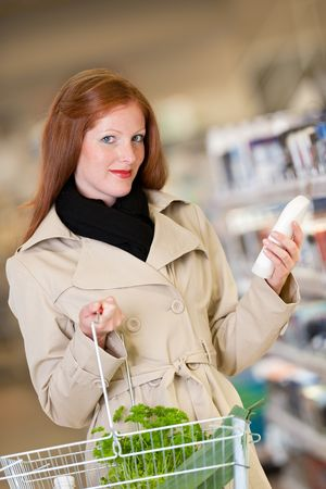 Red hair woman buying shampoo in a supermarket photo