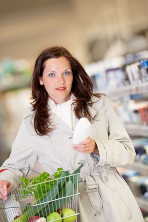 Young woman buying shampoo and holding shopping basket photo