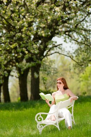 Red hair woman reading book on white bench in a meadow; shallow DOF photo