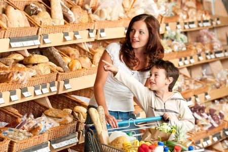 grocery cart: Woman with child in a supermarket choosing bread