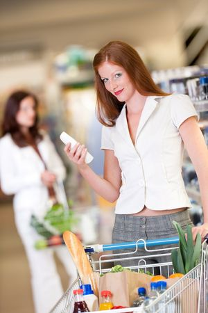 Red hair woman holding shampoo and shopping photo