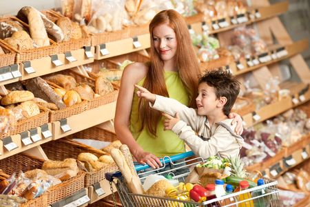 Red hair woman and child with a shopping cart photo